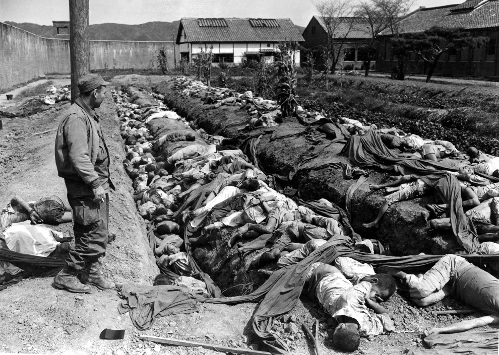 Bodies of some 400 Korean civilians in Taejon killed by retreating communist forces before U.S.-UN recapture of the city on Sept. 28. Looking on at left is Gordon Gammack, war correspondent of the Des Moines Register and Tribune. (AP Photo/James Pringle)